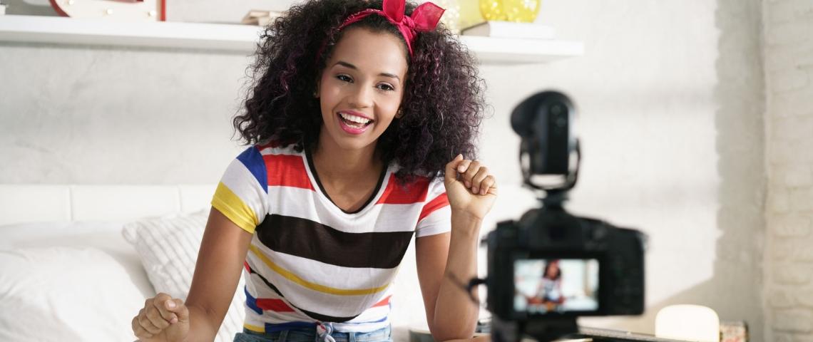 Une jeune femme métisse en train de se filmer dans sa chambre