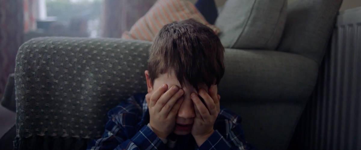 Un jeune garçon avec ses mains sur les yeux