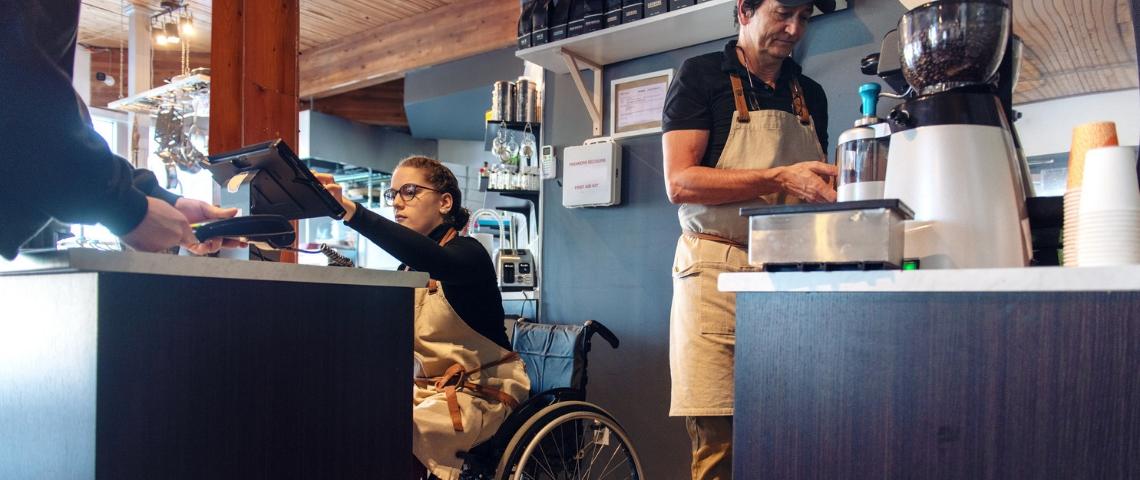 une personne en chaise roulante en train de servir un client au comptoir au restaurant