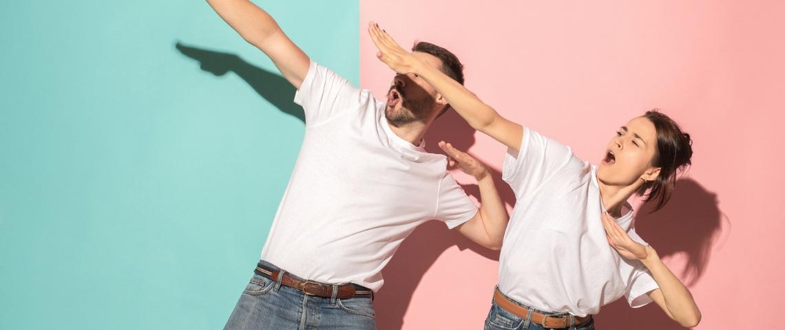 deux personnes en t-shirt blanc font des gestes de victoire sur fond bleu et rose