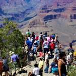 Des touristes regardent l'horizon au bord d'une falaise