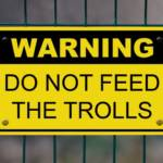 "Pancarte indique ""Warning do not feed the trolls"""