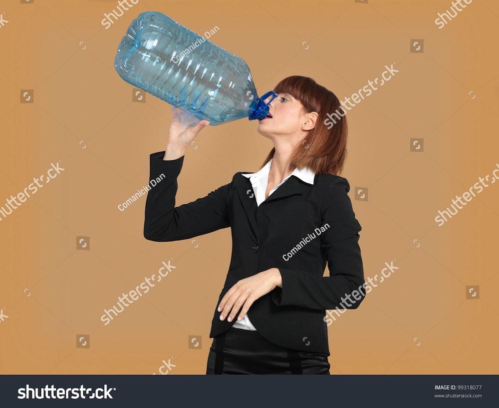 une femme boit la fontaine à eau à la bouteille