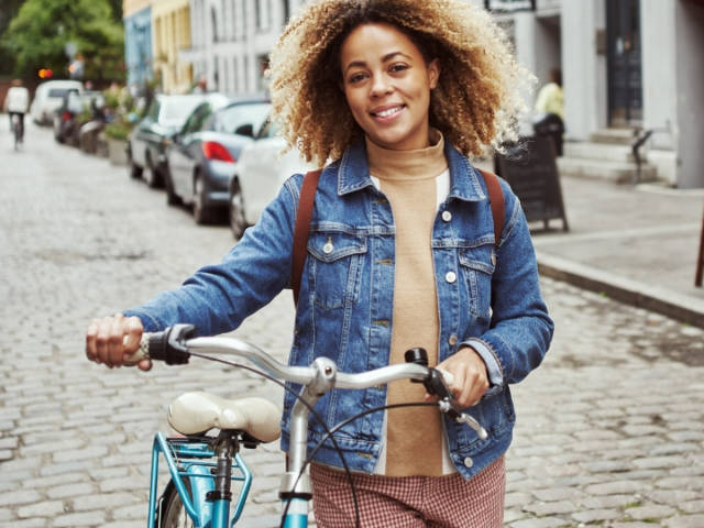 Une femme qui marche à côté de son vélo dans une ville
