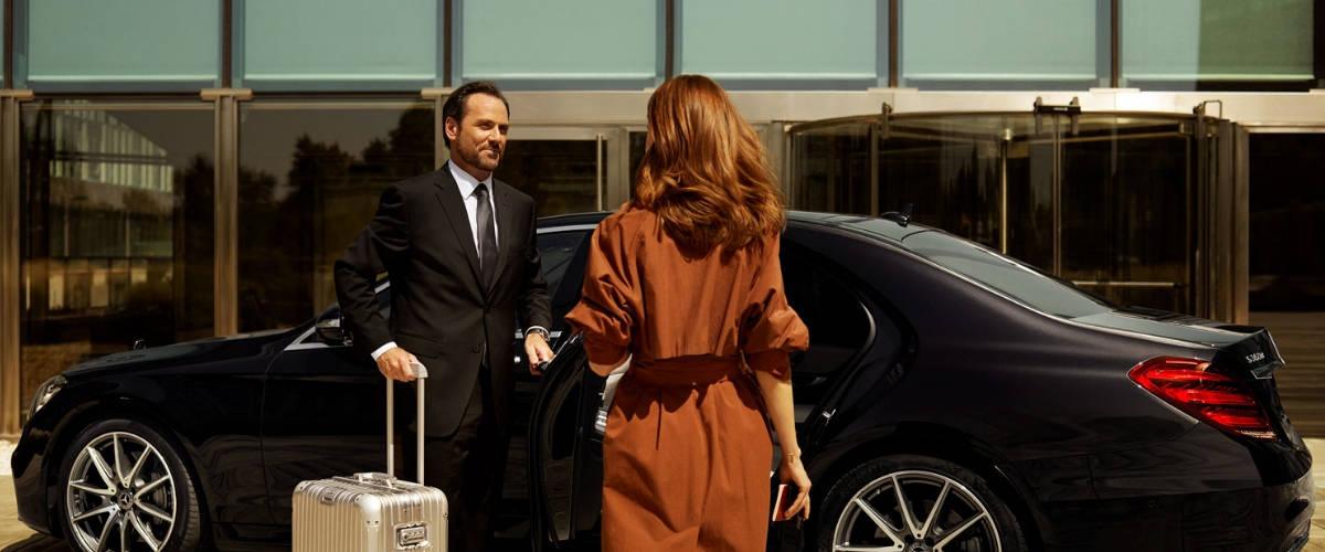 Femme en robe vers une voiture berline accompagnée d'un chauffeurs tenant sa valise