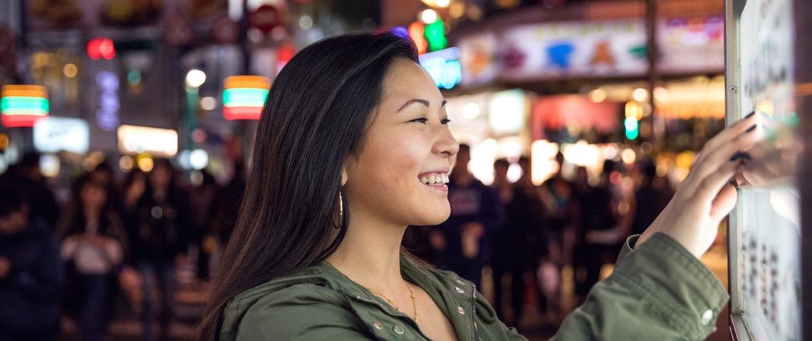 femmes touche un écran dans une grande ville