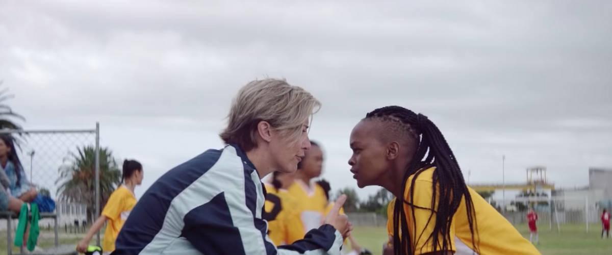 Une entraineuse discute avec un footballeuse