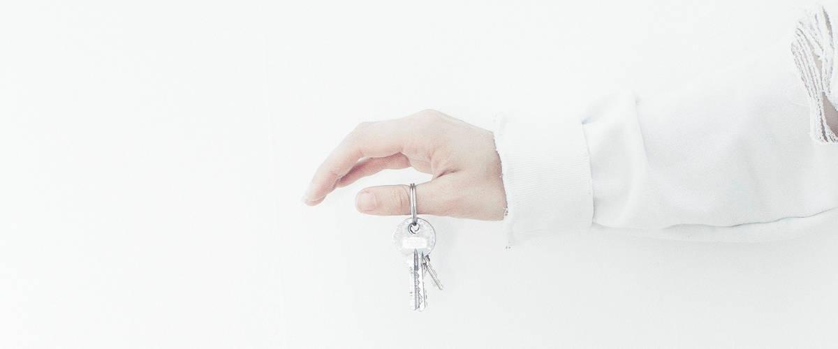 Une mùain sur fond blanc tient une clés