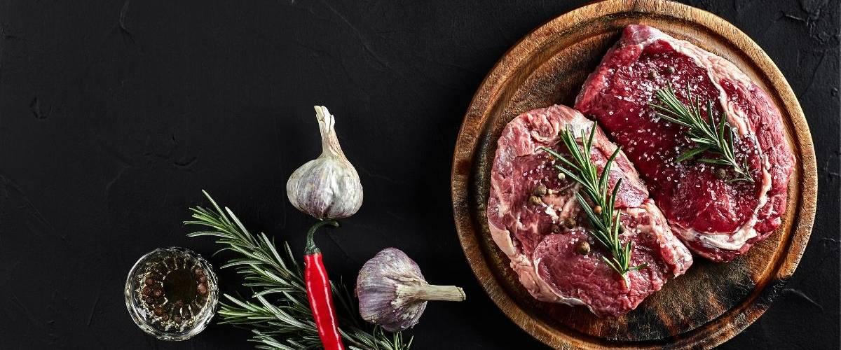 Deux morceaux de viande de boeuf placé sur une planche, sur une table en ardoise