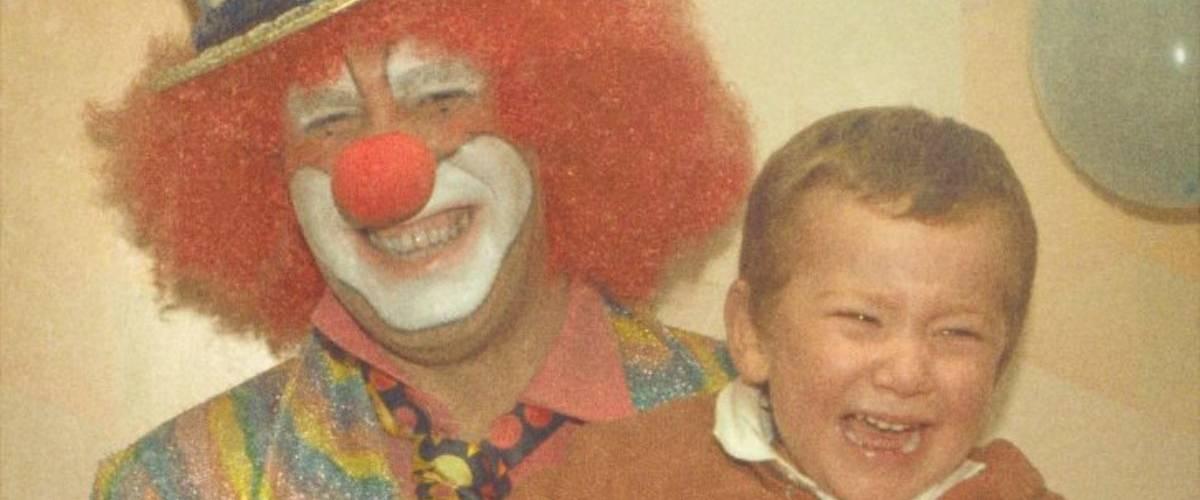 Un clown souriant tient un enfant en pleure