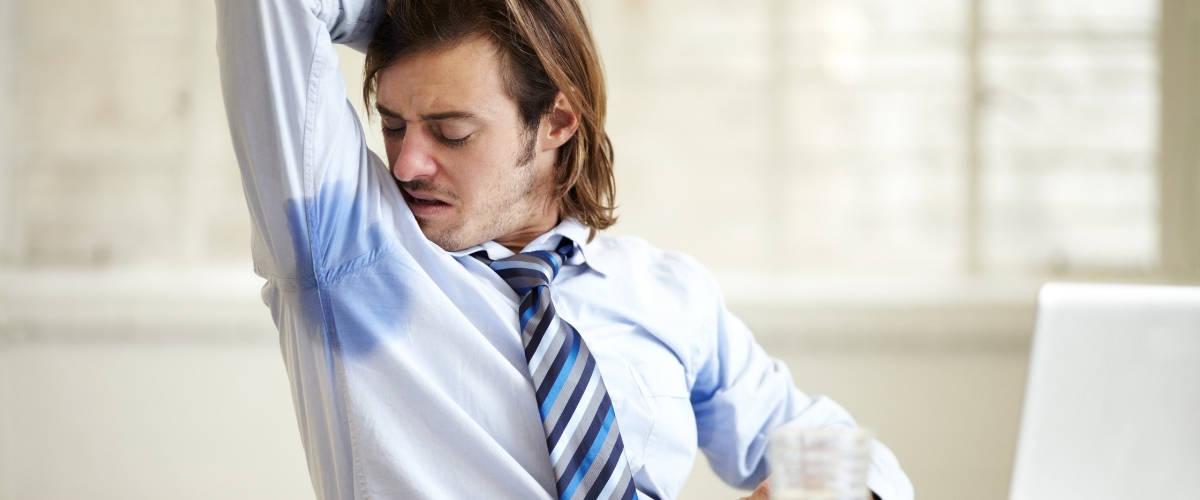 Un homme en chemise et cravate se sent les aisselles humides
