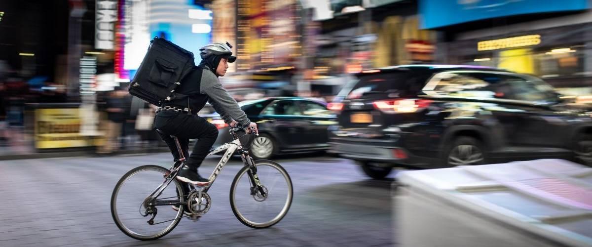 Un livreur en vélo, traverse un centre-ville
