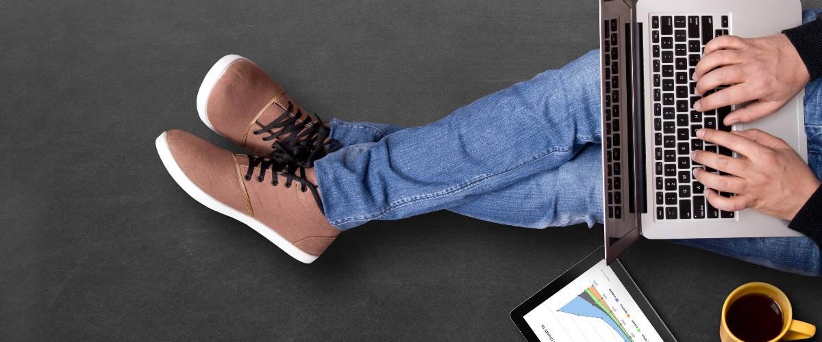 Un homme assis par terre en train de travailler sur son ordinateur portable