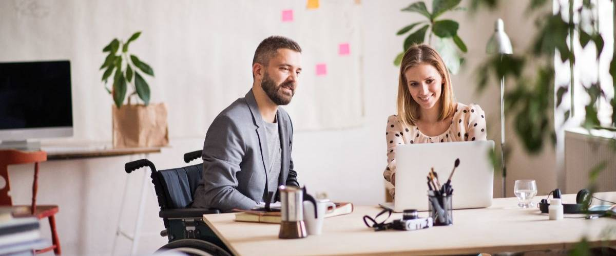 Une femme et un homme en fauteuil roulant discutent dans un bureau
