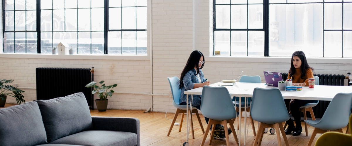 Deux jeunes femmes travaillent sur une table, dans un bureau