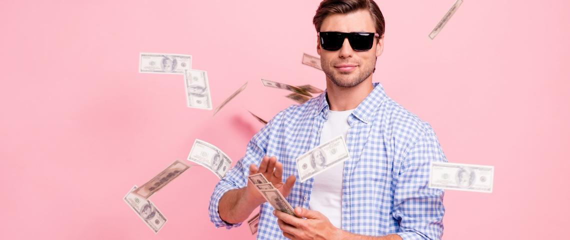 Un homme avec des lunettes de soleil en train de jouer avec des billets de banque