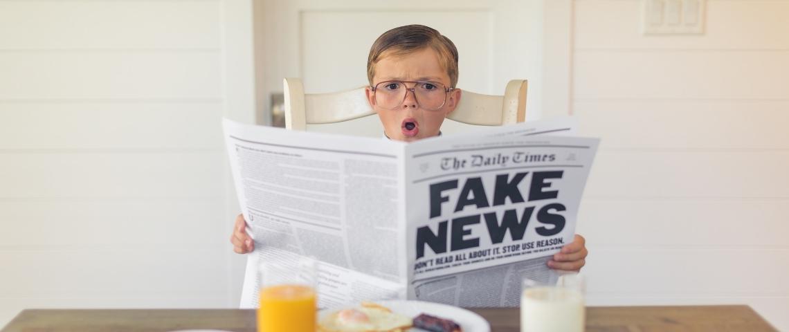 un enfant fait une tête outrée en lisant un journal