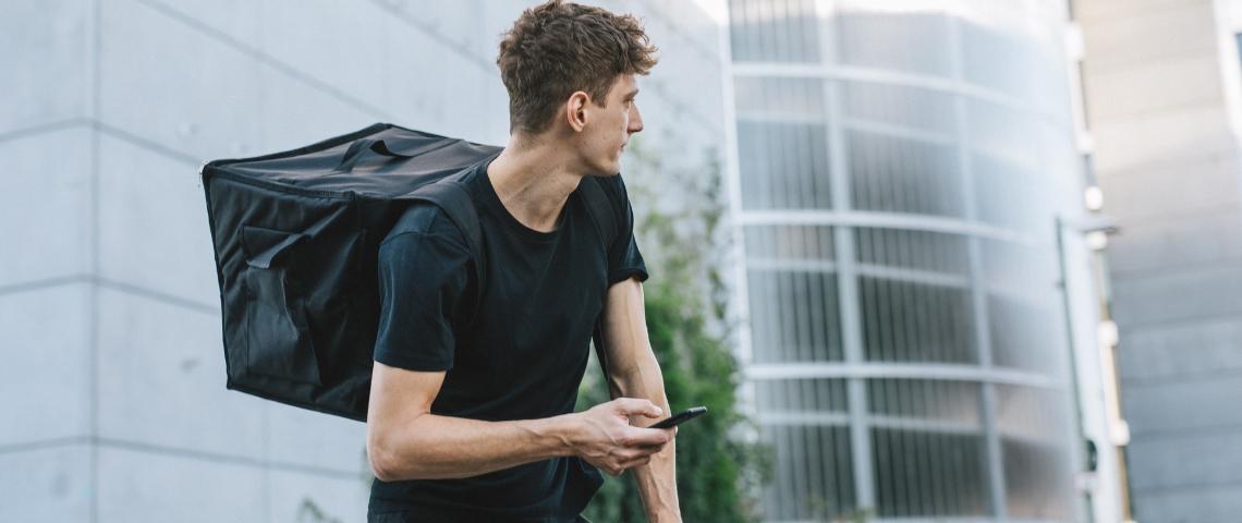 Un homme à vélo avec un sac à dos pour livrer des produits alimentaires
