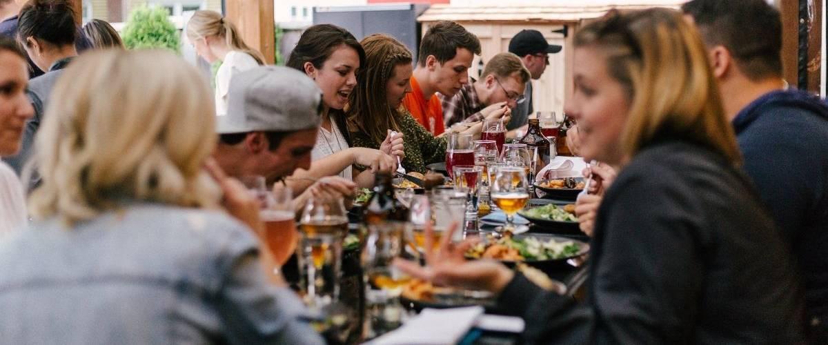 Un groupe d'amis dinent autour d'une table de restaurant fleurie et animée