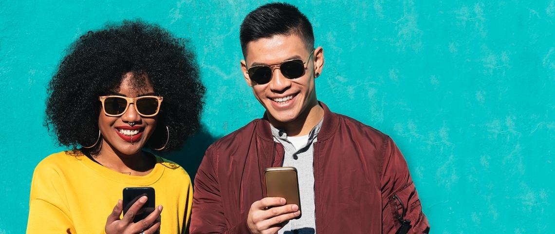 Deux amis heureux devant leur smartphone.
