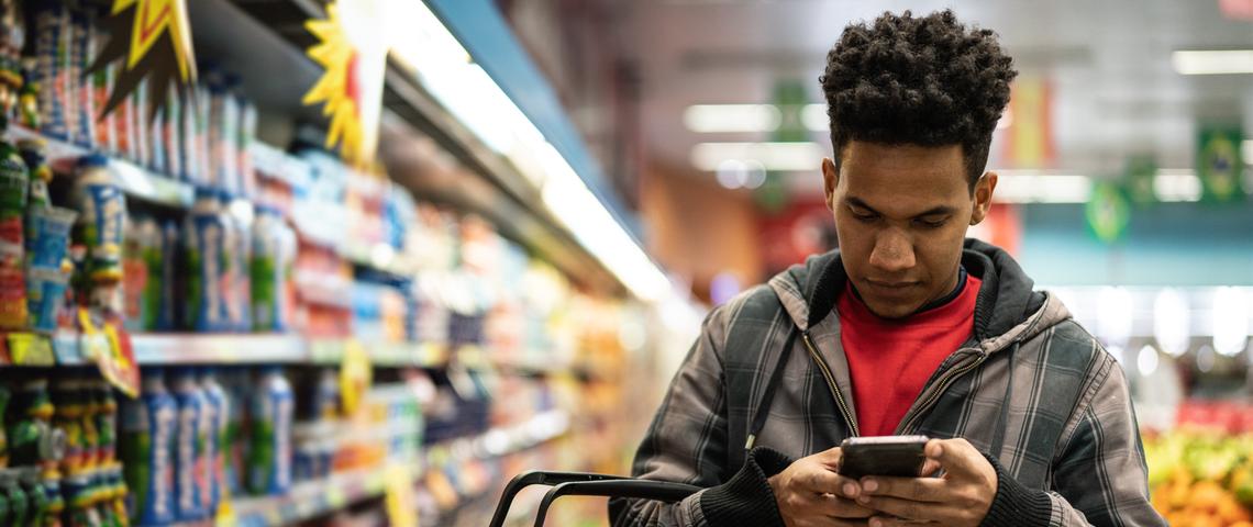 Homme au supermarché consulte son smartphone