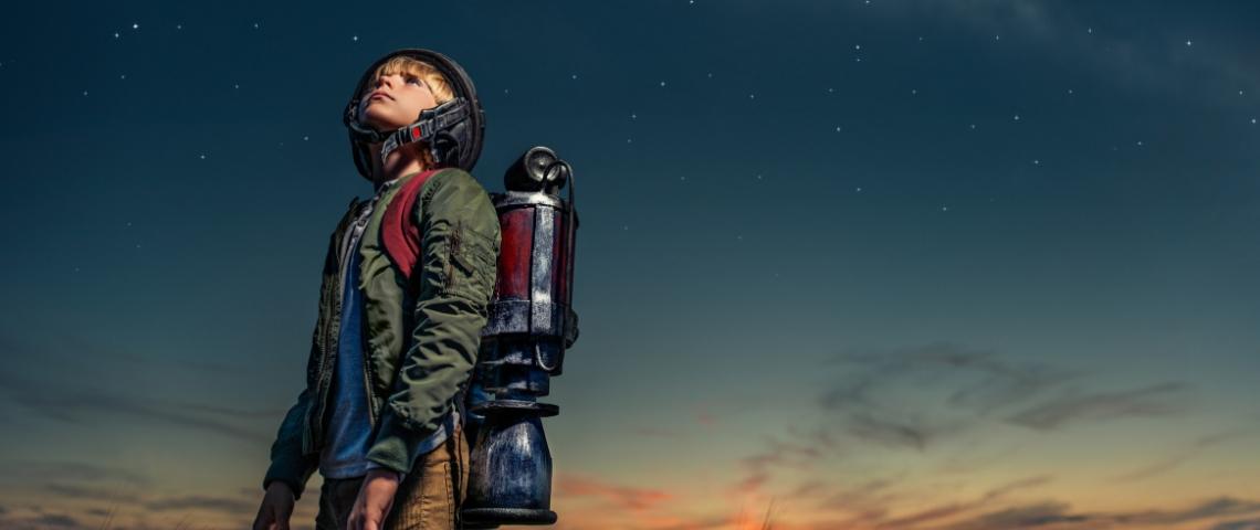 un enfant avec une fusée dans le dos regarde les étoiles