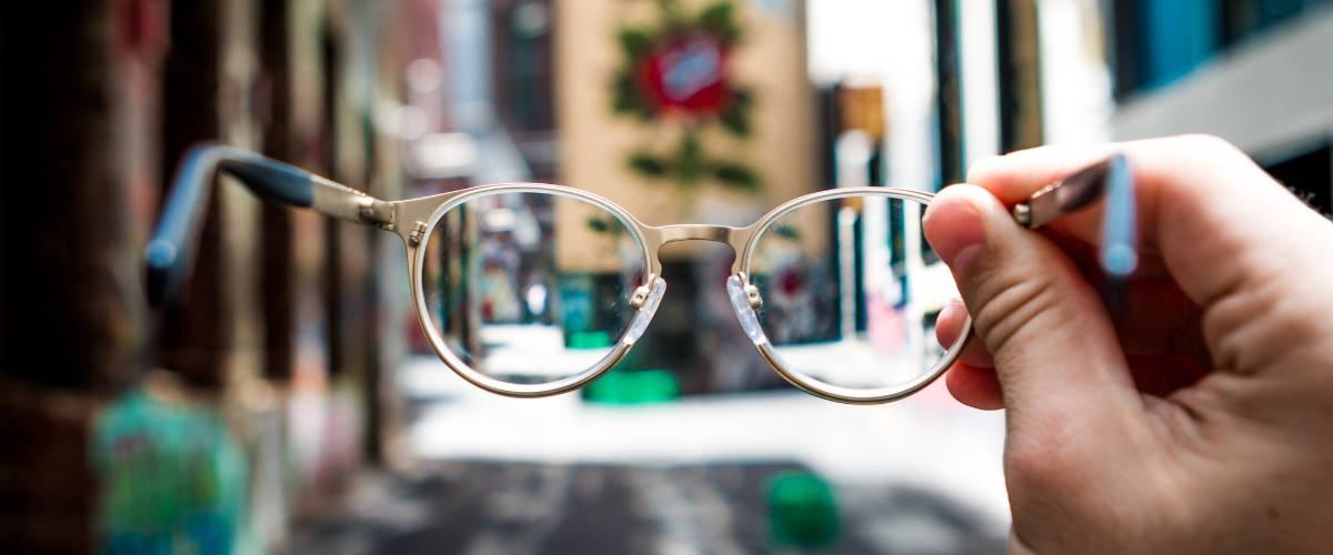 Une main tenant une paire de lunettes dans une rue