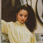 Une femme avec une chemise jaune dans une laverie vintage