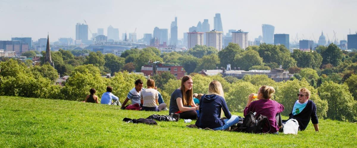 Des gens assis dans un parc avec la ville de Londres à l'horizon