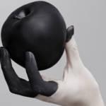 Une main dont les doigts sont colorés en noir tenant une pomme peinte en noir