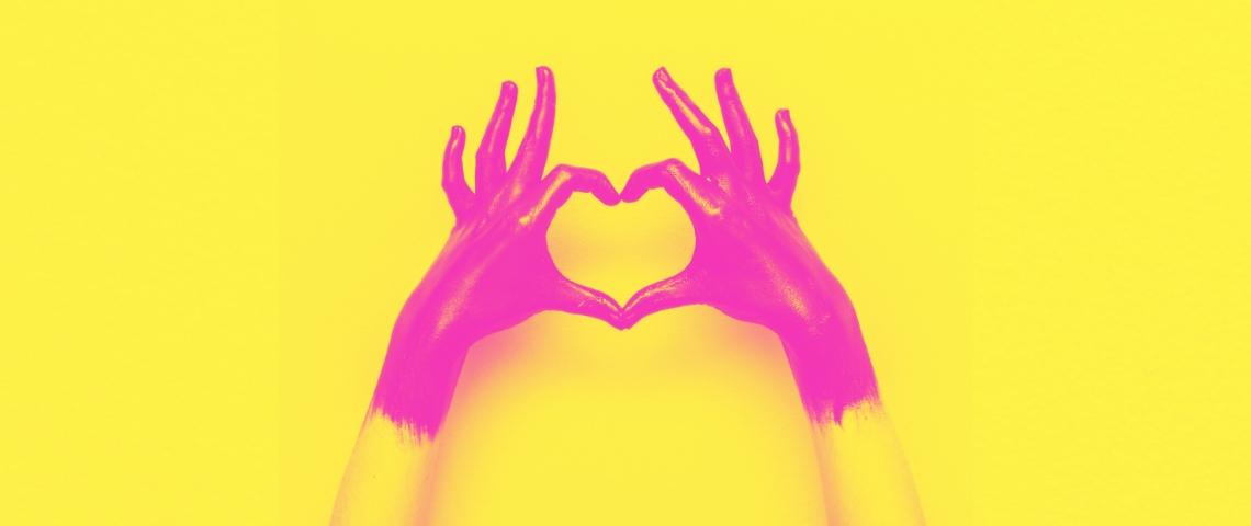 Des mains paintes en rose et jaune en train de former un coeur avec les doigts