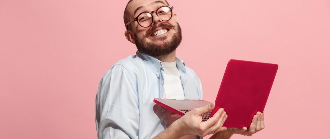 Un homme à lunettes est heureux avec son ordinateur portable