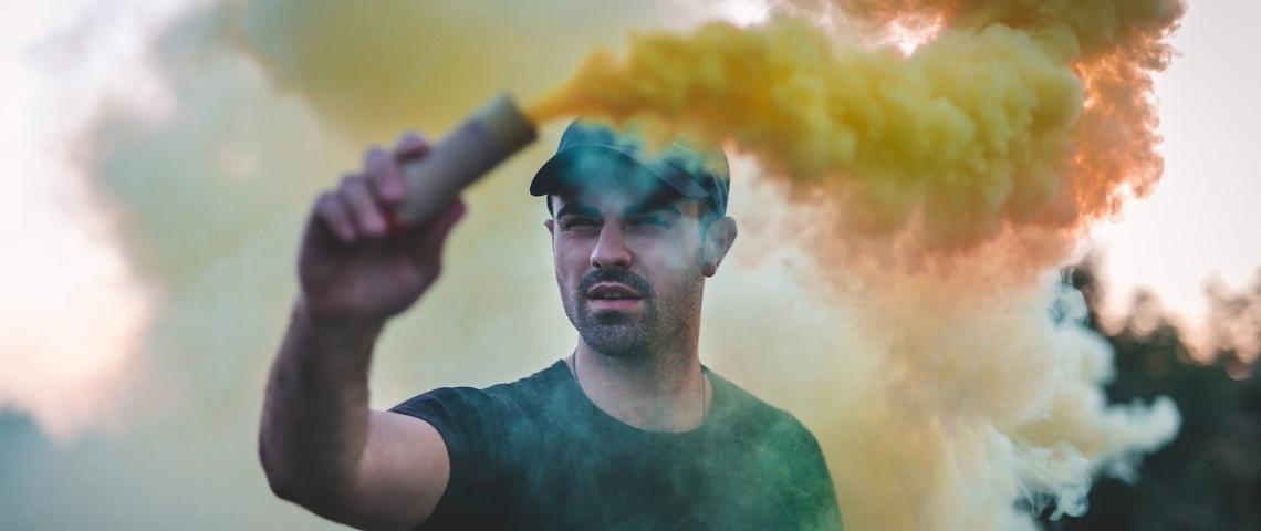 Un jeune brandit une bombe de fumée colorée