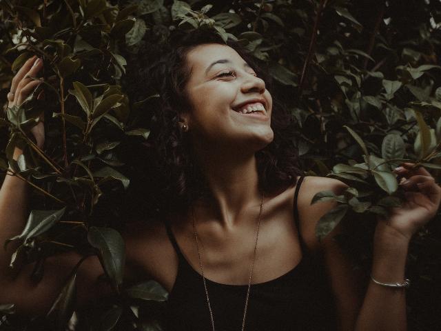 Une femme souriante dans des feuillages