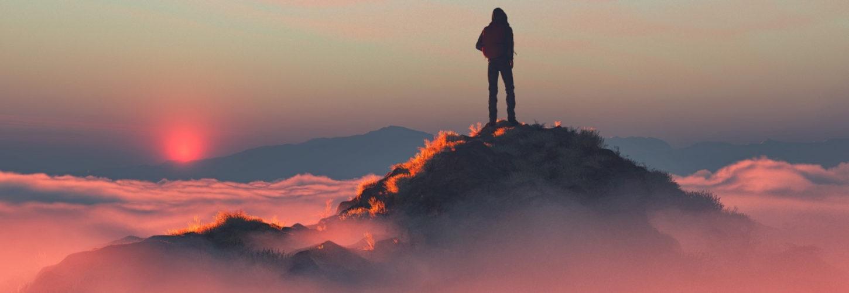 Un homme au sommet d'une montagne au dessus des nuages roses