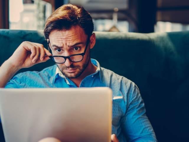Un homme perplexe devant son ordinateur