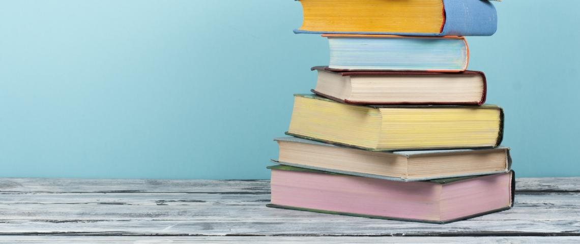 Une pile de livres aux couleurs pastels sur un fond bleu