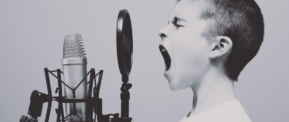 Un petit garçon en train de crier dans un micro, en noir et blanc
