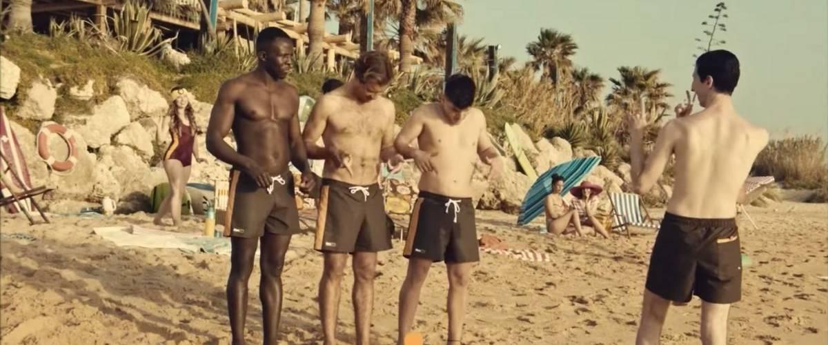 Trois hommes sur une plage, portent des maillots Pornhub