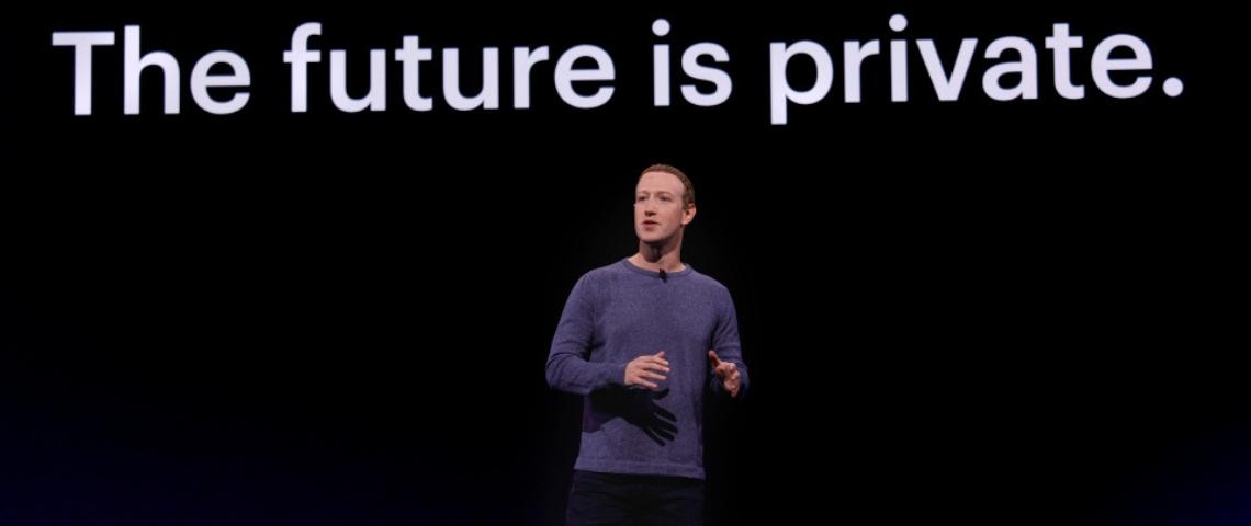 un homme devant un écran noir sur lequel il est écrit The future is private