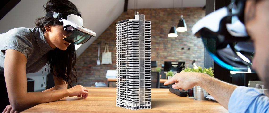 deux personnes équipée de casque de réalité augmentée travaille autours d'une maquette de building