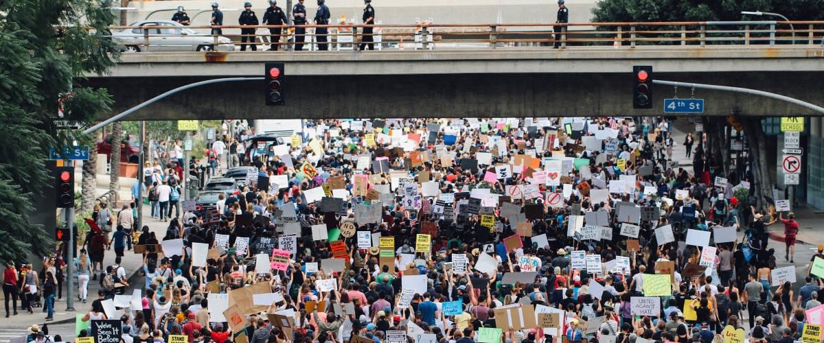 Une foule de manifestants traverse le dessous d'un pont.