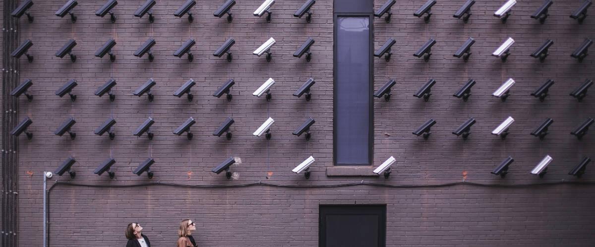 deux femmes regardent un mur de caméra de surveillance