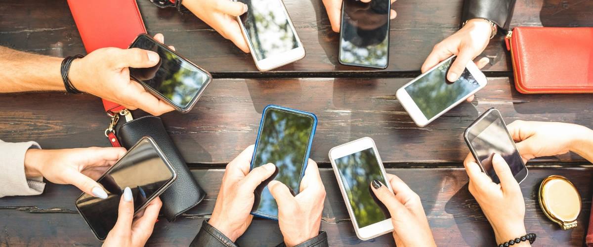 Des mains avec des smartphones autour d'une table
