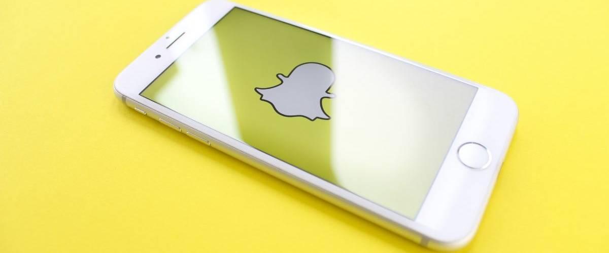Un smartphone posé sur un fonsd jaune, avec sur son écran le logo du réseau social Snapchat