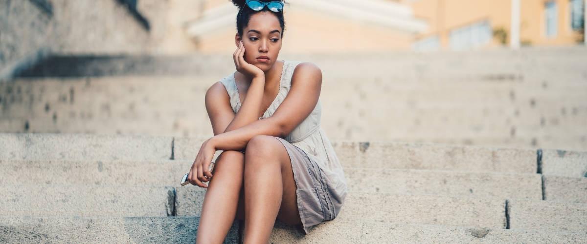 Une femme assise seule sur un escalier