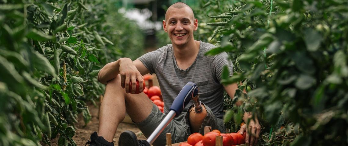 Homme portant une prothèse de jambe dans une serre de tomates.