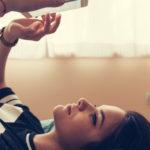 Une adolescente allongée sur son lit en train de lire d'envoyer des textos