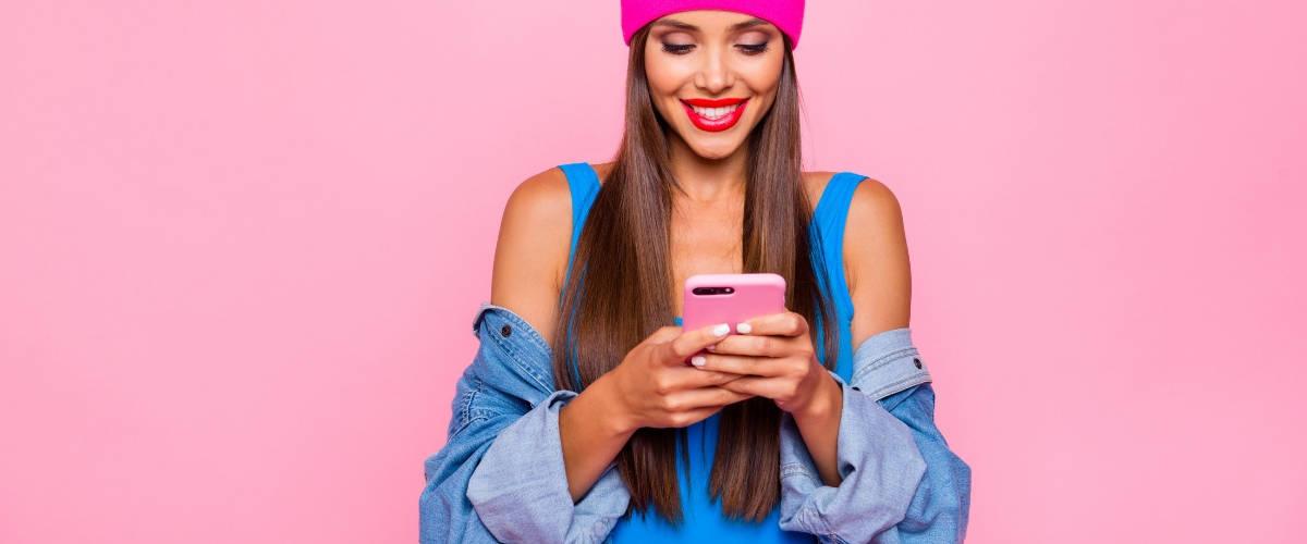 Une femme en train d'écrire sur son smartphone devant un fond rose