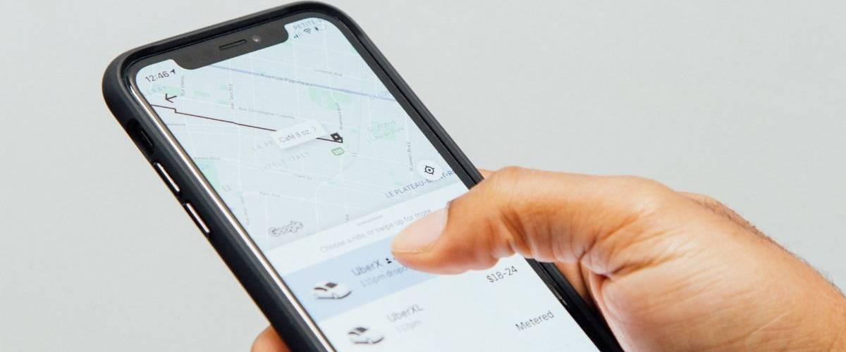 Une main d'homme, sur le point de commander un chauffeur Uber, sur l'application de la compagnie
